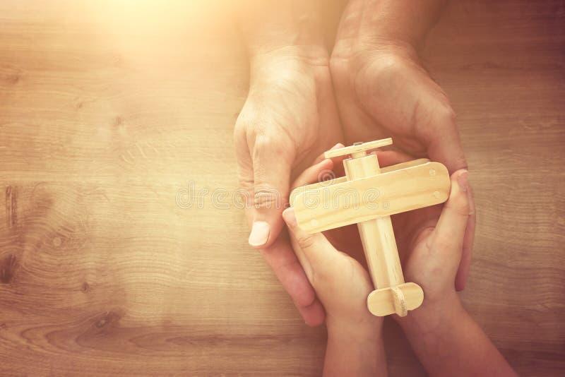 Foto de padre y niño sujetando juntos un avión de juguete de madera Feliz día de padre y concepto de vacaciones vista superior, a foto de archivo libre de regalías