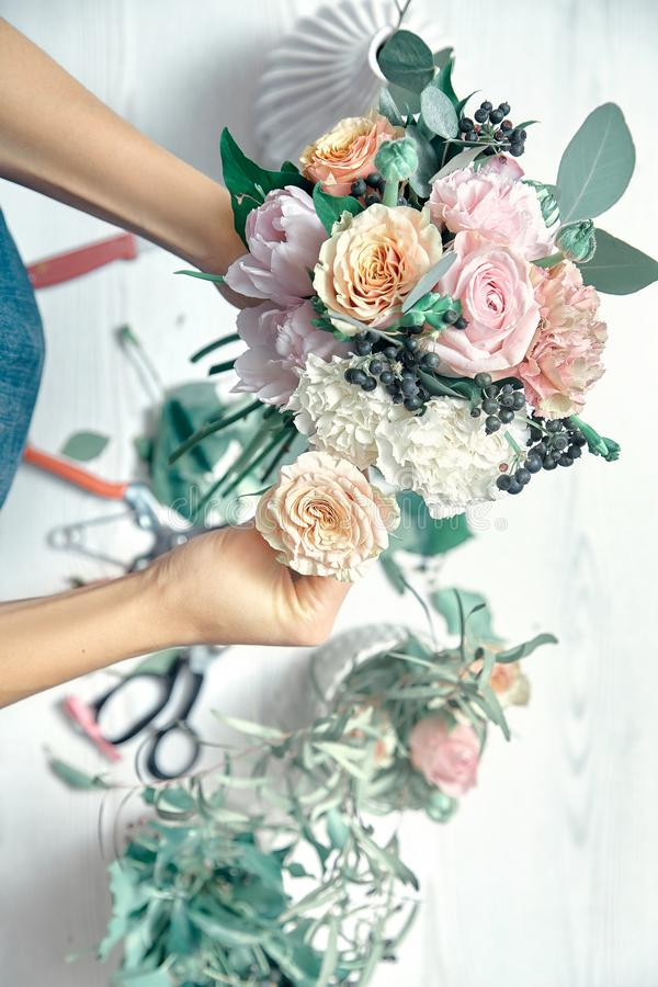Imagem vertical da florista feminina no trabalho Arranjar várias flores em bouquet Vista superior Professor de licenciatura em me fotografia de stock
