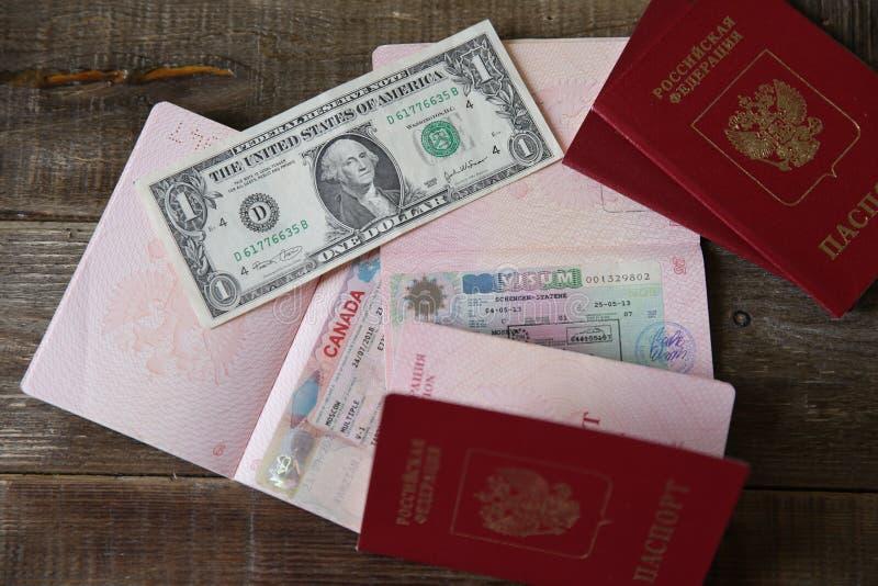 Rosyjski paszport z wizą i pieniędzmi kanadyjskimi i Schengen - jeden dolar. Paszport podróżny z wizą. Wakacje i podróże obrazy stock