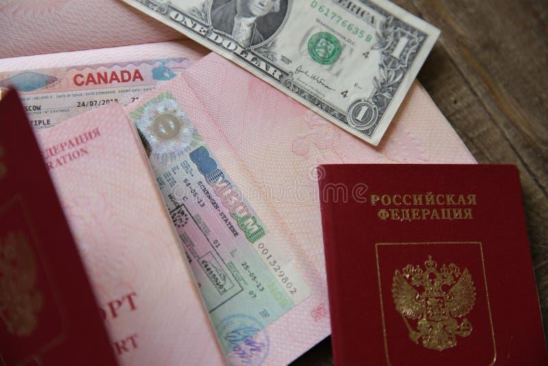 Rosyjski paszport z wizą i pieniędzmi kanadyjskimi i Schengen - jeden dolar. Paszport podróżny z wizą. Wakacje i podróże fotografia royalty free