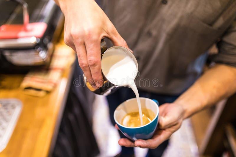 Strålning av hanhänder som häller mjölk och bereder färska cappuccino Koffertartist och beredning Morgonkaffe royaltyfri bild