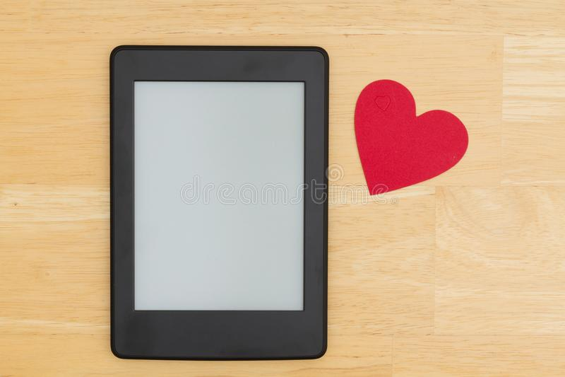 An e-reader on a wood desk with a heart. A blank e-reader on a desk with a heart that you can use as a mock up for your message stock photo