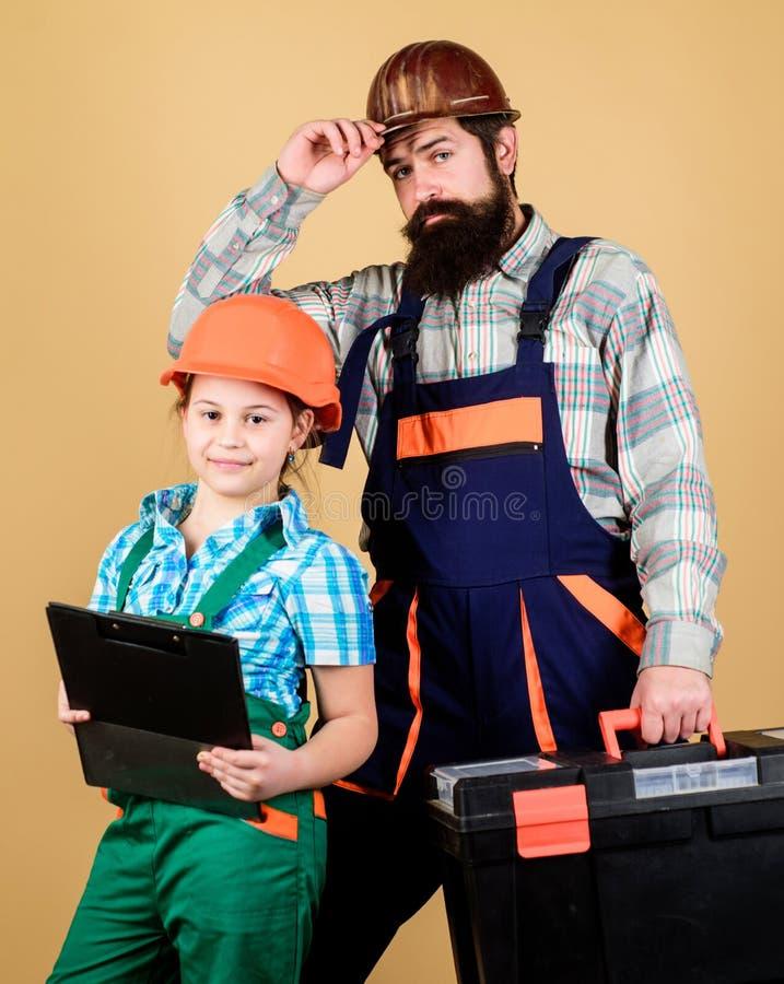 E Reparador en uniforme Ingeniero Hombre barbudo con la niña Trabajador de construcción imágenes de archivo libres de regalías