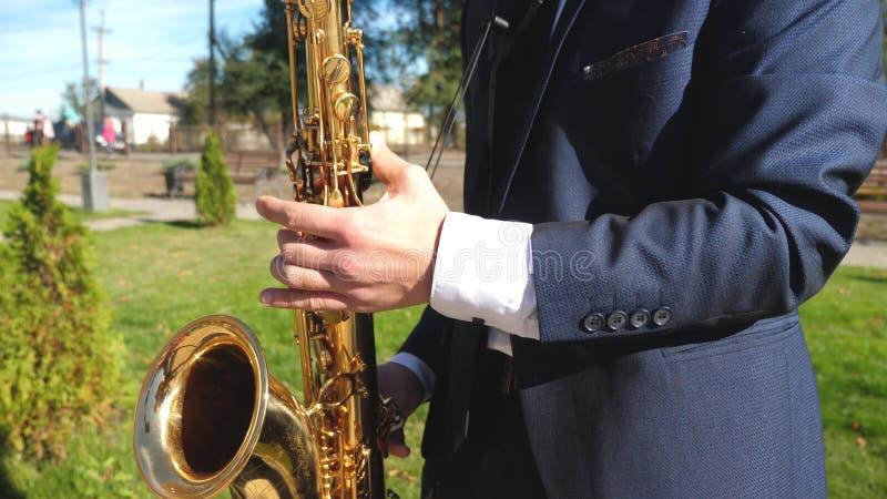 E Saksofonista w obiadowej kurtki sztuce na złotym saksofonie Żywy występ fotografia stock