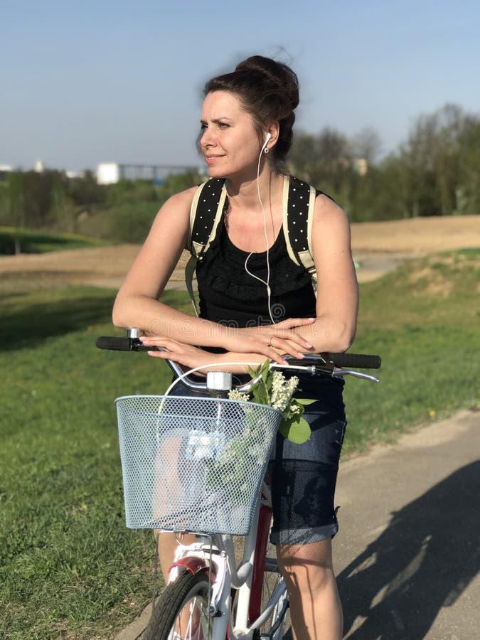 E Se sienta en una bicicleta, detr?s de una mochila tur?stica Los dientes de le?n est?n floreciendo, hierba joven son fotos de archivo libres de regalías
