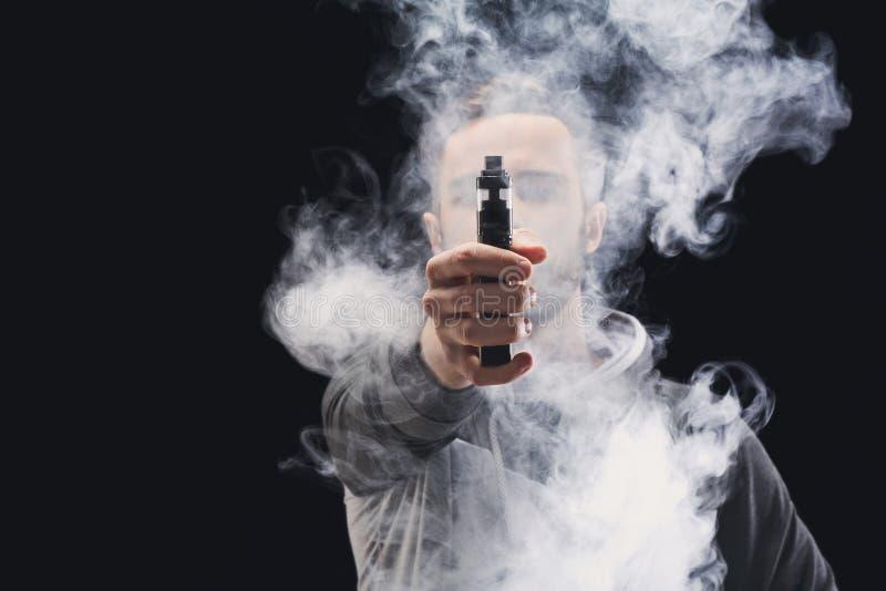 E-sigaretta vaping del giovane con fumo sul nero fotografie stock
