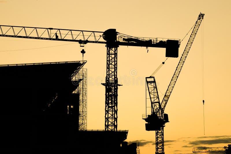 E siluetta del gruppo della gru a torre della costruzione con il fondo del cielo di tramonto immagini stock