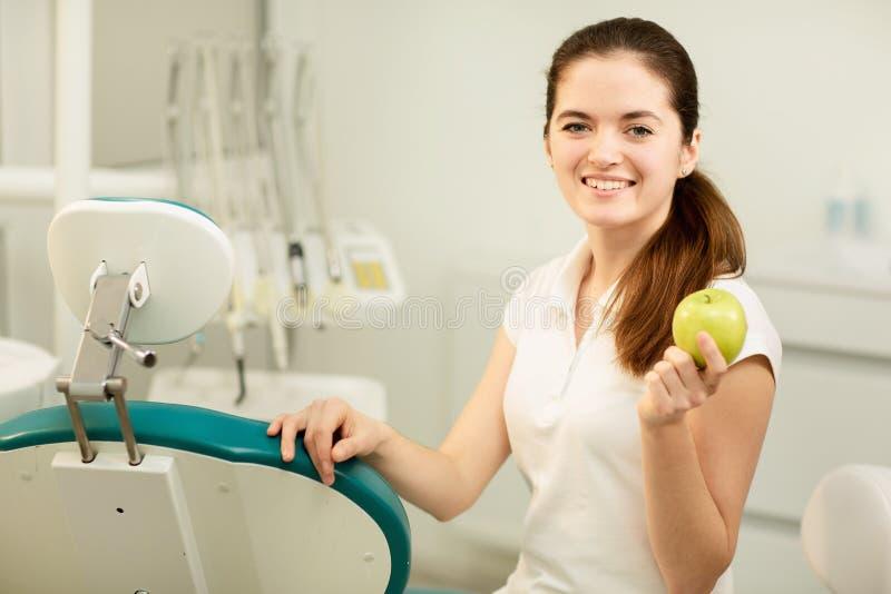 ?e?ski dentysta u?miecha si? i trzyma zielonego jab?ka, stomatologicznej opieki i zapobiegania poj?cia zdjęcie stock