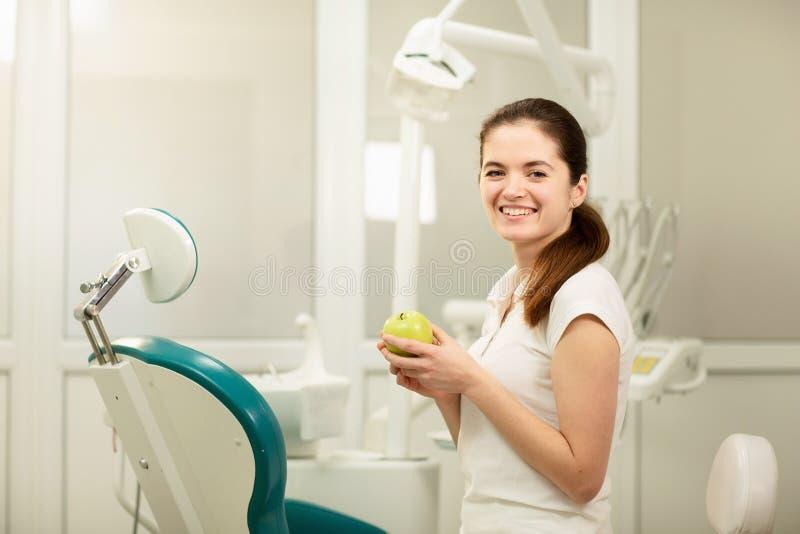 ?e?ski dentysta u?miecha si? i trzyma zielonego jab?ka, stomatologicznej opieki i zapobiegania poj?cia obraz royalty free