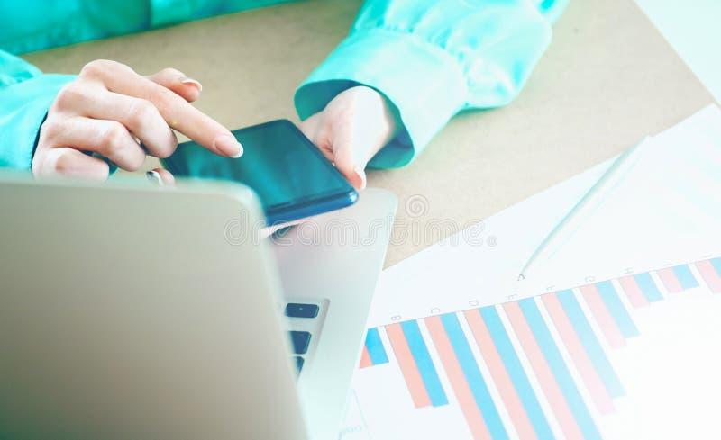 ?e?ski r?ka chwyt?w smartphone wskazuje palcowego ekranu sensorowego telefon, laptop?w pieni??ni wykresy na tle fotografia stock