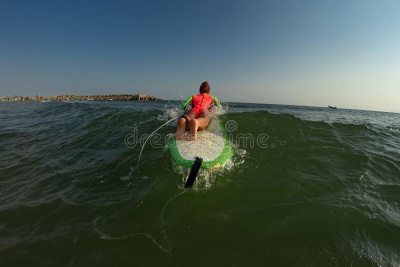 ?e?ski surfingowiec na jej surfboard w wodzie fotografia royalty free