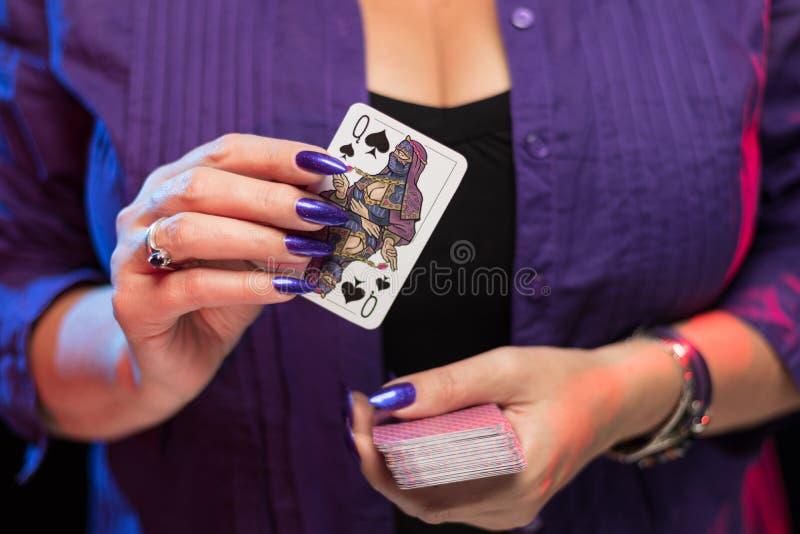 ?e?skie r?ki z purpurowym manicure'em trzymaj? pok?ad sztuk karty obraz royalty free