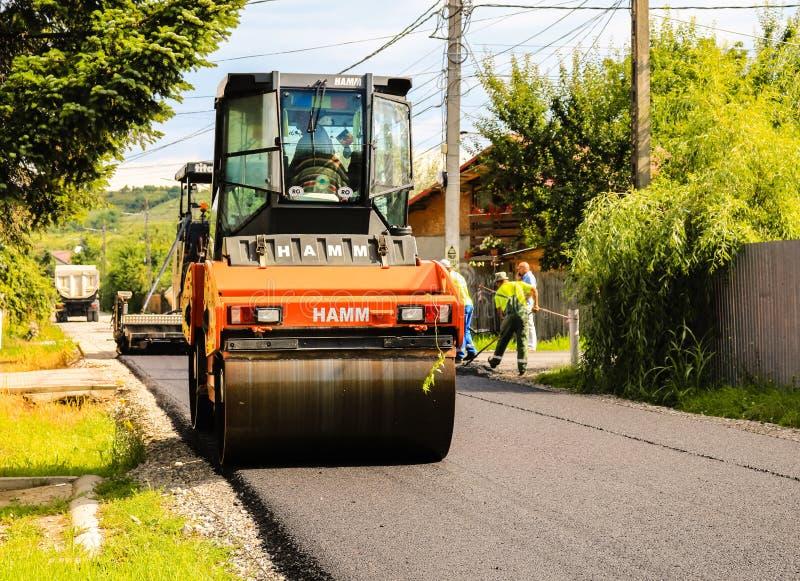 E Sluit omhoog foto van een oranje wegwals die het nieuwe asfalt met een stortplaatsvrachtwagen en een asfalt samenpersen royalty-vrije stock foto