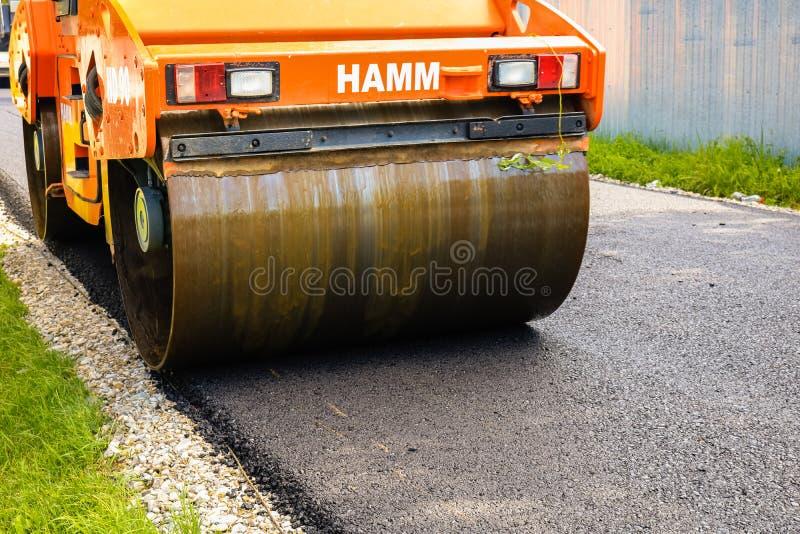 E Sluit omhoog foto van een oranje wegwals die het nieuwe asfalt samenpersen Aanleggen van een nieuwe weg met stock afbeelding