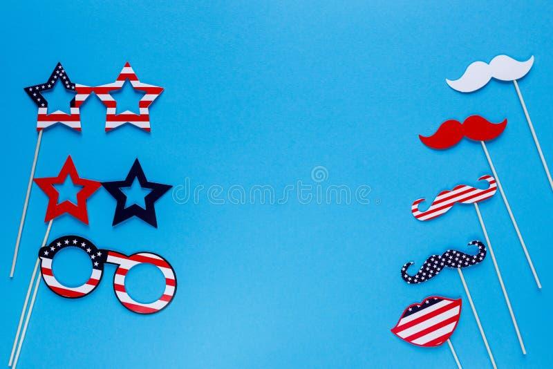 E Snorren, lippen, glazen op stokken op blauwe achtergrond Amerikaanse vlagkleuren De achtergrond van de onafhankelijkheid Day stock foto's