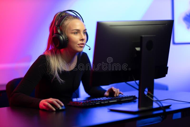 E-sport Gamer Girl com fone jogando videogame online no PC fotografia de stock royalty free