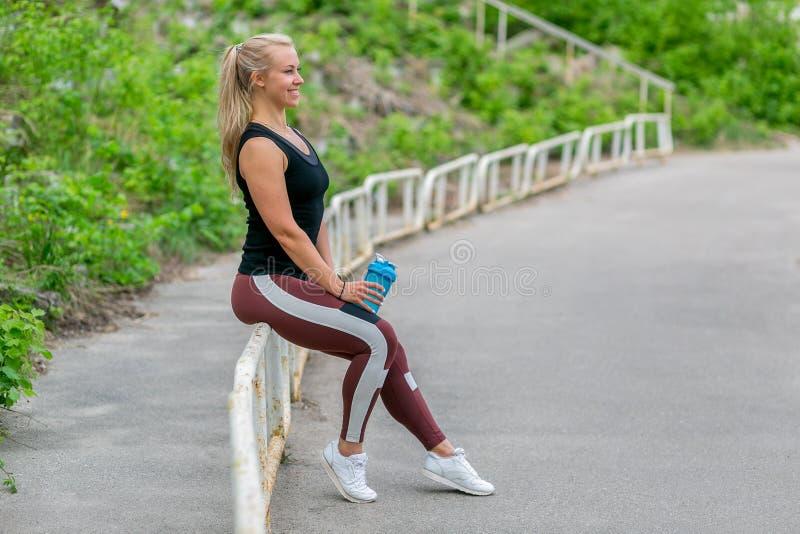 E Sportieve jonge vrouwenzitting op traliewerk en holding een waterfles na een training Training bij het stadion stock afbeeldingen