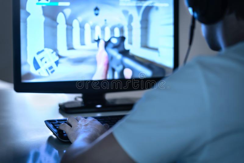 E sports and gaming concept. Gamer playing FPS video game with computer and wearing headphones. Professional videogame player. royalty free stock images