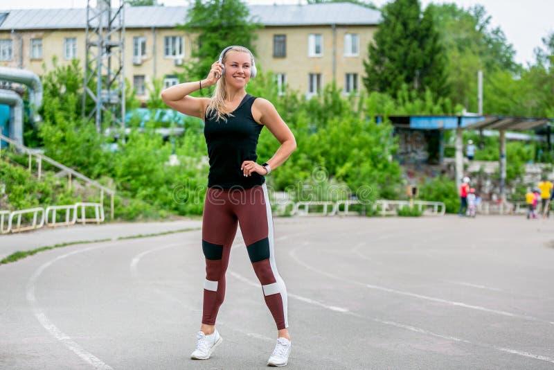 E Stelt de sporten jonge vrouw in de volledige groei in hoofdtelefoons Training bij het stadion Gezond het levensconcept horizont stock afbeeldingen