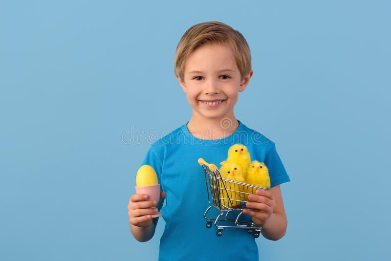 E Uśmiechnięta blond chłopiec, 6 lat, trzyma żółtych jajka zdjęcie stock