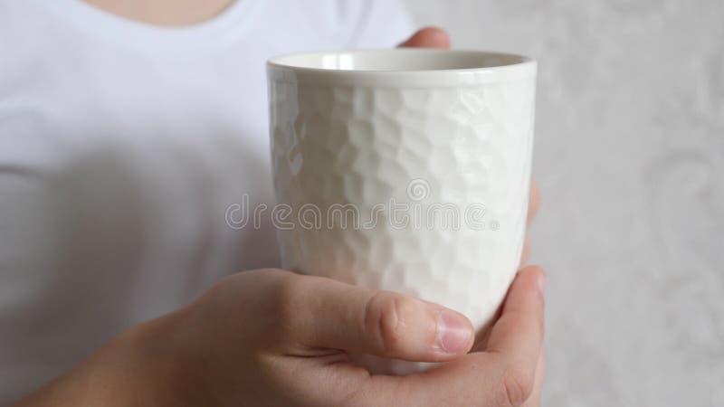 E Una bella ragazza irriconoscibile romantica che beve una bevanda calda in un accogliente fotografie stock