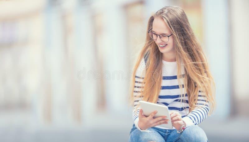 E Ung skolflicka med skolapåsen och minnestavlaapparaten royaltyfria bilder