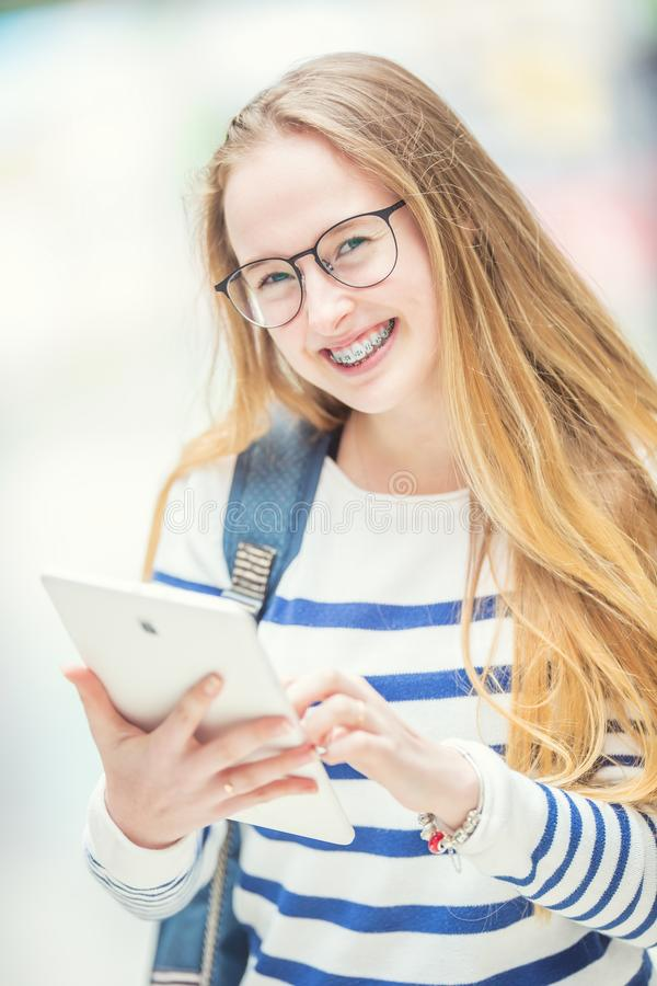 E Ung skolflicka med skolapåsen och minnestavlaapparaten royaltyfri fotografi