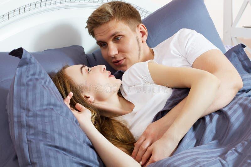 E Unga vuxna heterosexuella par som ligger p? s?ng i sovrum arkivbild