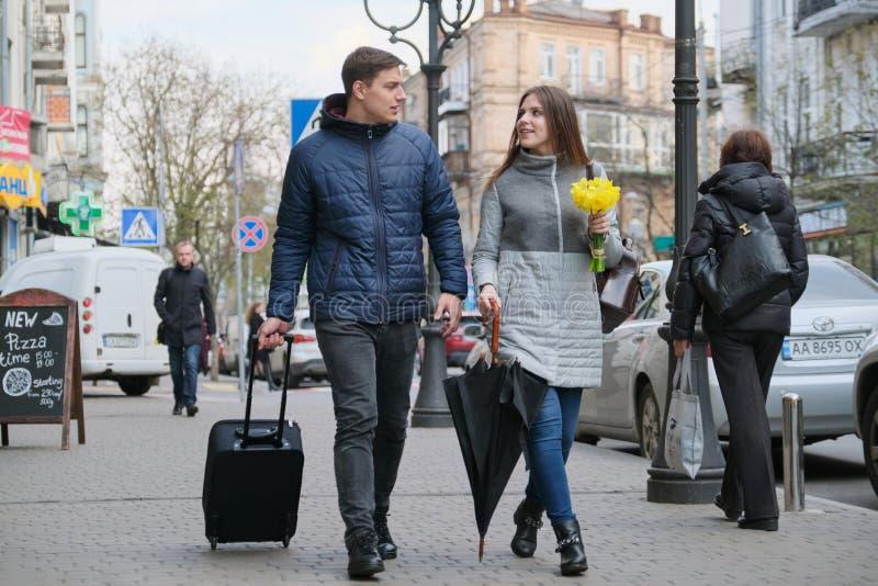 E Utomhus- stående av unga par som går med resväskan på stadsgatan, lycklig ung man och kvinnalopp in royaltyfri foto