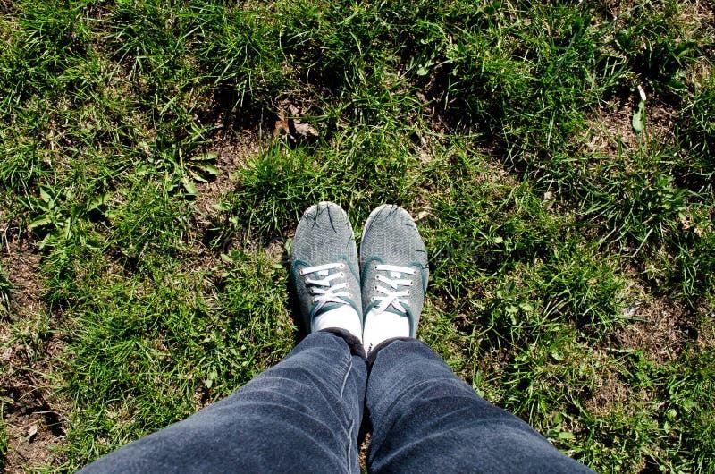 E Viaje Viajero de las piernas Hierba Hierba verde r Ponga verde la ciudad Vaqueros y zapatillas de deporte r foto de archivo