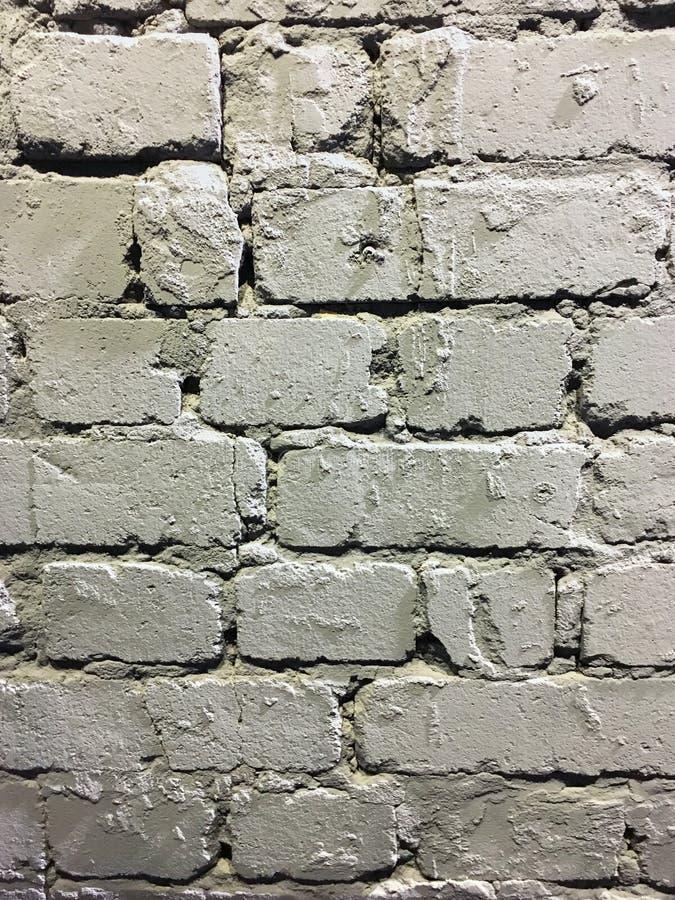E Vieux mur de briques lav? par blanc avec le pl?tre in?gal souill? et minable r images libres de droits