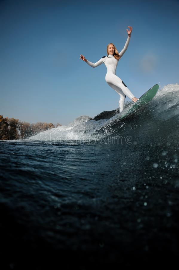 Side view blonde girl standing on the wakeboard. E view beautiful blonde girl in the white swimsuit standing on the wakeboard rising her hands stock photos