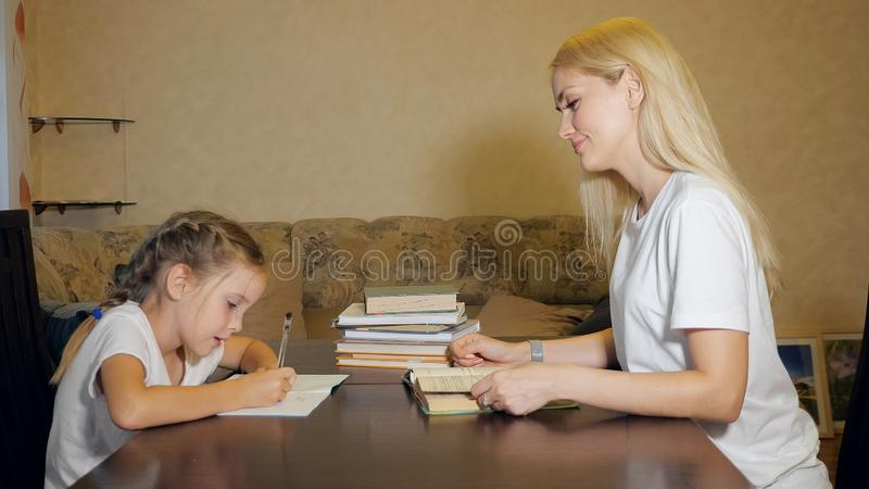 Woman helping little girl with homework royalty free stock image