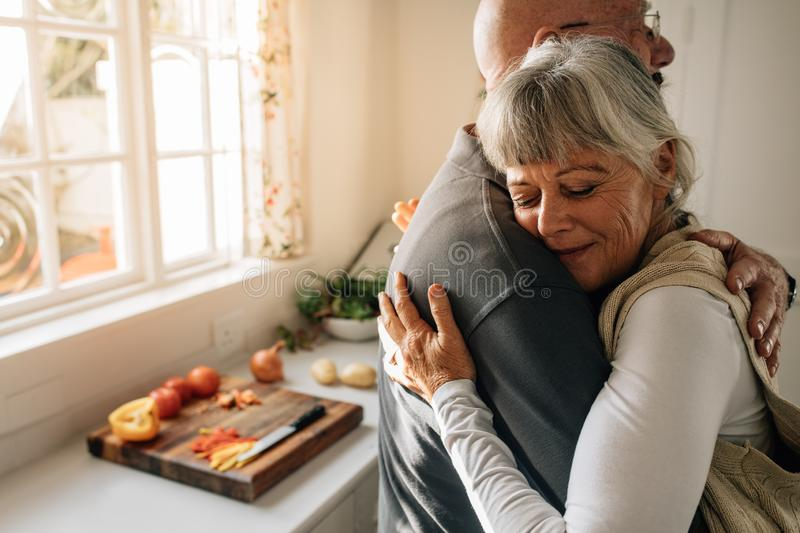 Side view of an elderly couple hugging each other at home. Senior woman embracing her husband with closed eyes standing in kitchen stock photography