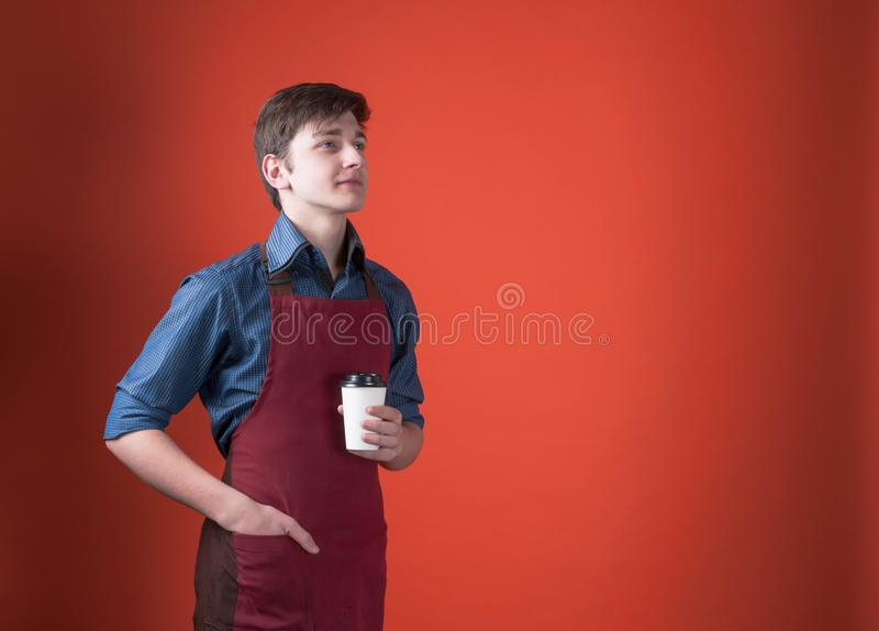 Handsome barista with dark hair in red apron holding paper cup with coffee and looking away on coral color background. E view of handsome barista with dark hair royalty free stock photography