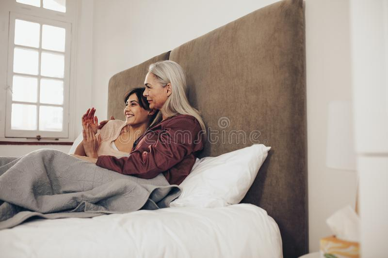 Side view of happy mother and daughter sitting on bed together. Smiling woman sitting beside her elderly mother and clapping her stock image