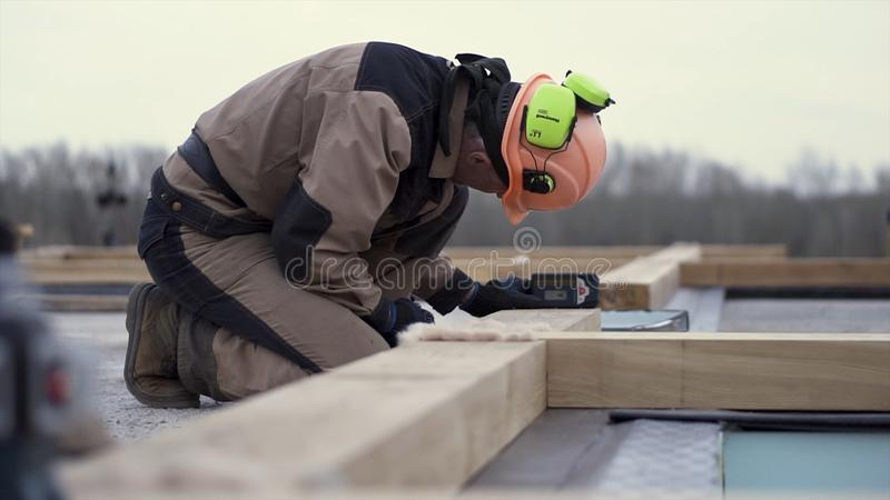 Side view of a man worker in uniform and protective helmet setting laser level tool at the construction site. Clip. Male stock images
