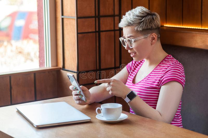 Side view portrait of excited young blogger with short hair in pink t-shirt is sitting in cafe, holding phone and making video royalty free stock photo