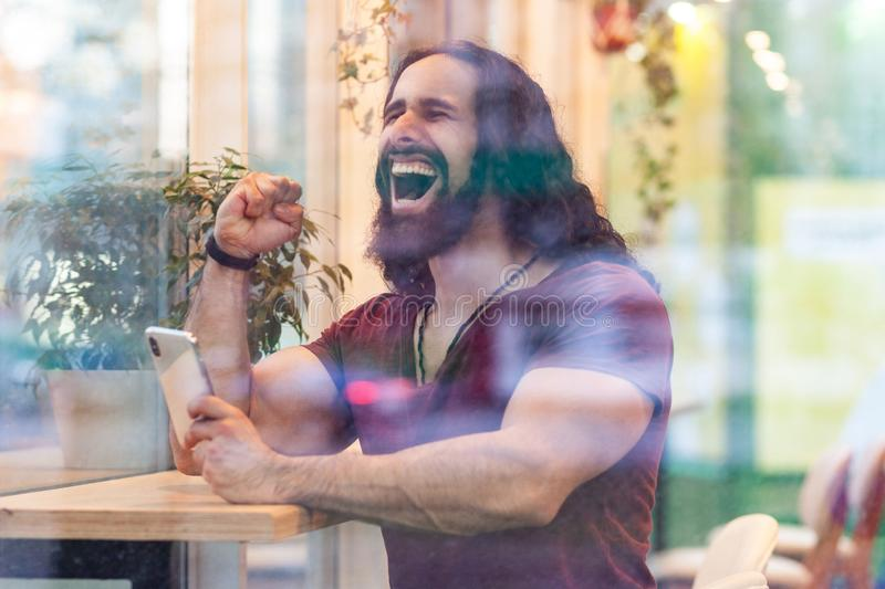 Side view portrait through the window of satisfied handsome young adult sporty champion man with curly long hair sitting on cafe,. E view portrait through the stock images