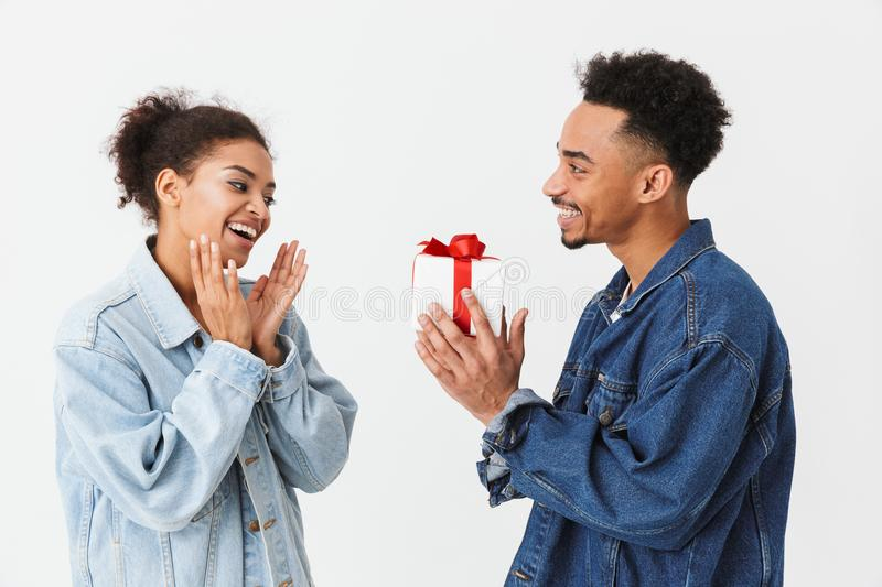 Side view of Smiling african man giving gift box stock photo