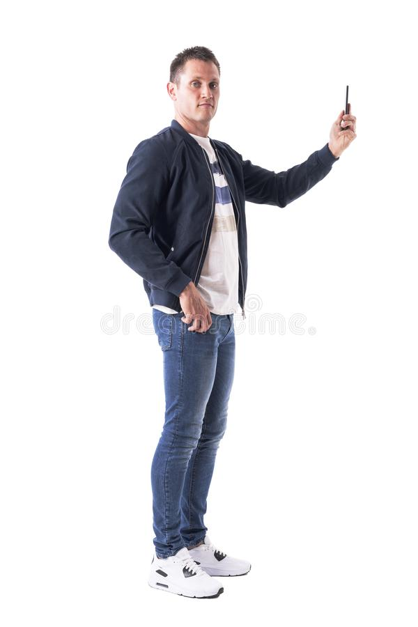 Side view of young man taking photos with mobile phone and looking at camera. royalty free stock images
