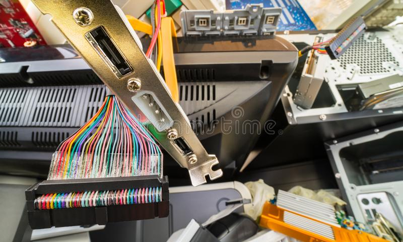 E-waste heap detail from used computer components. Colorful flat parallel cable from floppy disk drive, discarded serial interface for hard disc, old monitor, PC stock photography