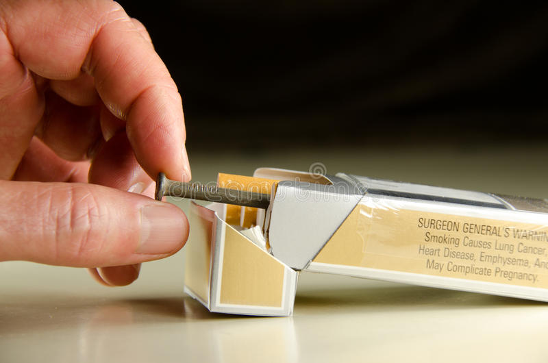 Each cigarette is a nail in your coffin. Closeup of a man pulling a nail out of a pack of cigarettes illustrating the dangers of smoking and reminding us that royalty free stock images