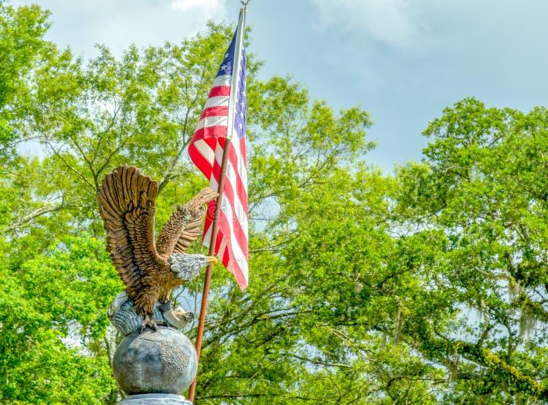 Eagel na kuli ziemskiej z flaga amerykańska zmrokiem i drzewami chmurnieje zdjęcia stock