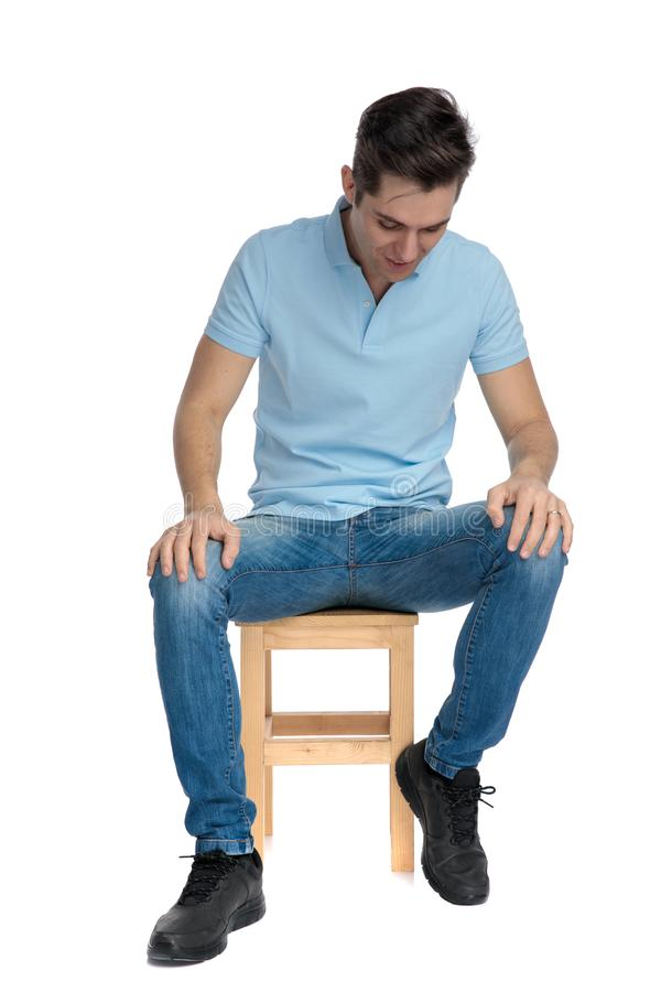 Eager casual guy looking down and smiling. While wearing blue jeans and shirt, sitting on a chair on white studio background royalty free stock photos