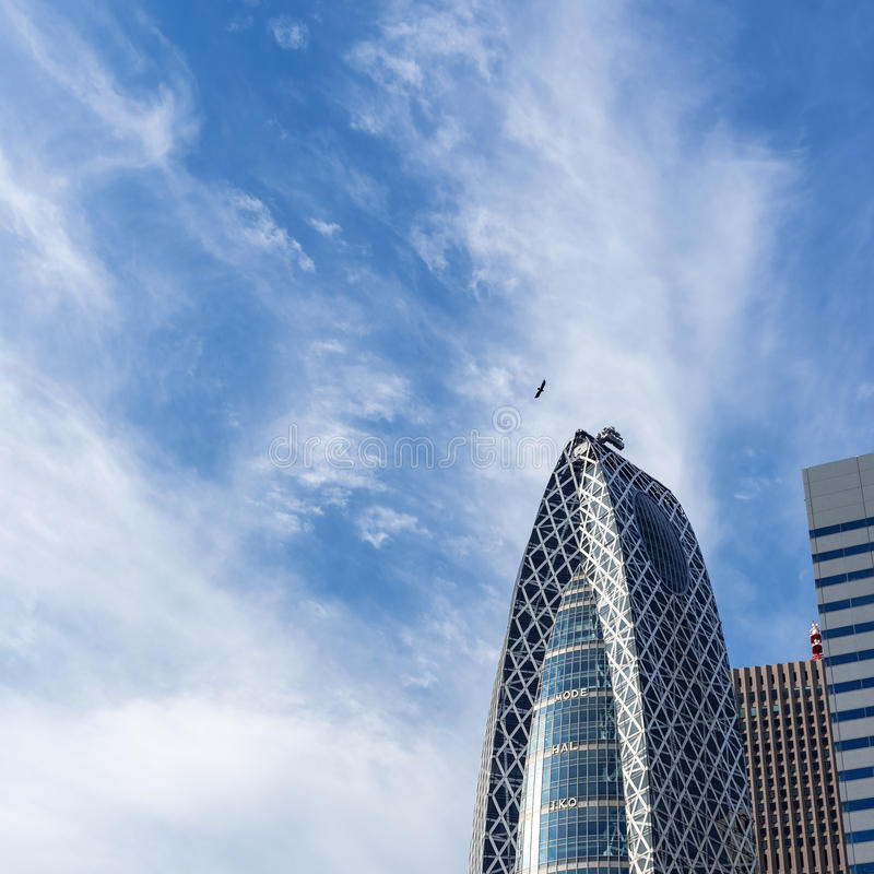 Eagle against modern city skyline. Eagle soaring above modern buildings in city skyline against blue skies on sunny day royalty free stock image