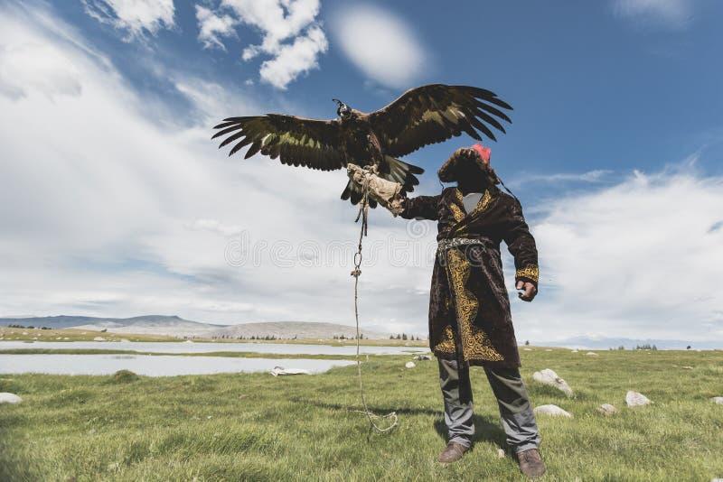 Eagle Hunter innehav guld- Eagle, medan fördela dess stora vingar arkivbild