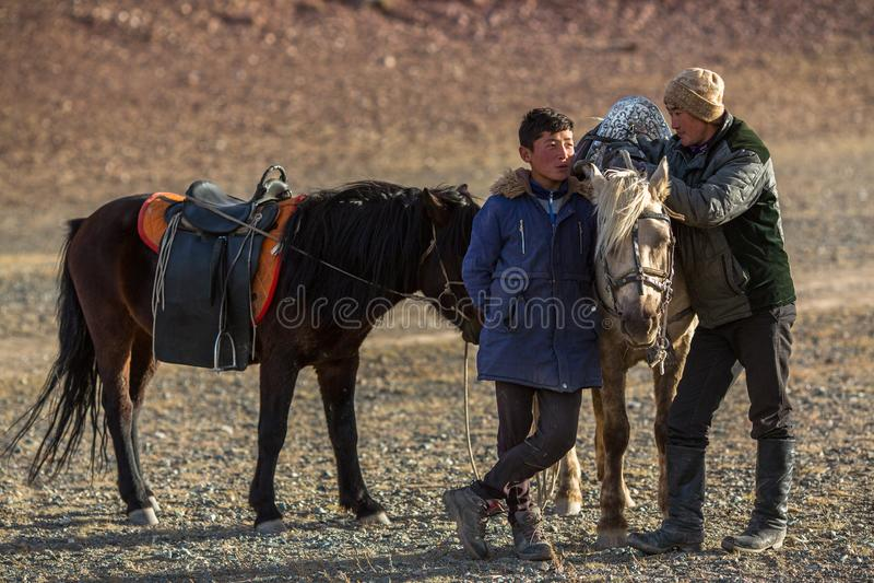 Eagle Hunters för unga män anseende nära deras hästar under jakt i bergöknen av västra Mongoliet arkivfoton