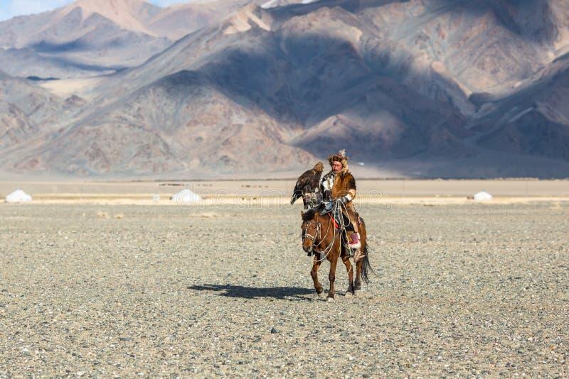 Eagle Hunters traditionella kläder, medan jaga till den haren rymma guld- örnar på hans armar royaltyfri bild