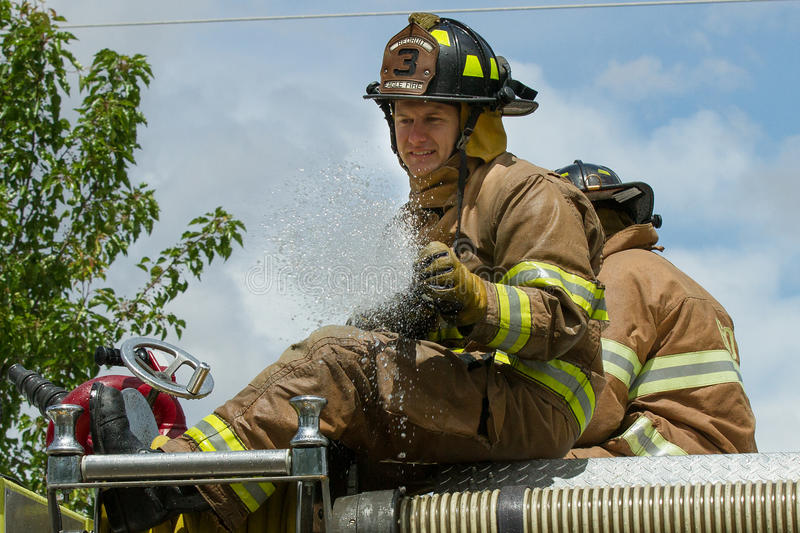 EAGLE/IDAHO - 9 JUNI: Brandweerman bovenop zijn firetruck nadat hij enkel zijn firehose tijdens de Eagle Fun-dagen in Eagle, Idaho stock afbeelding
